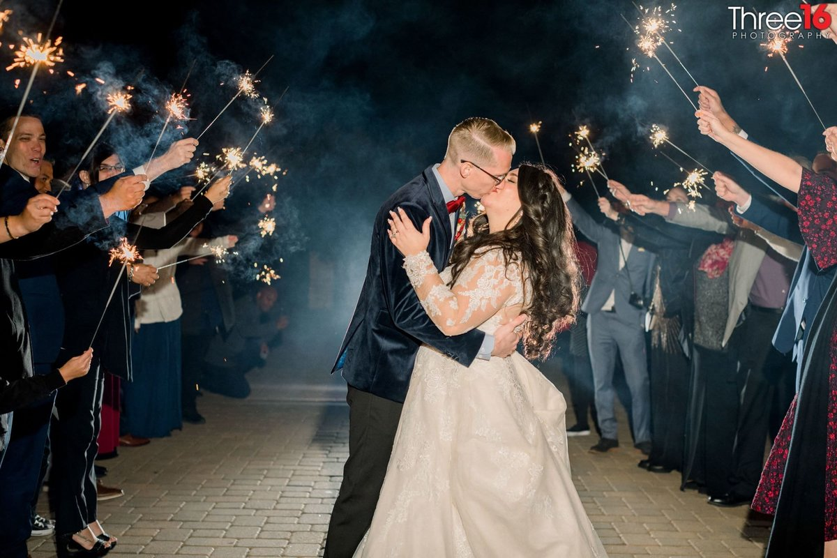 Bride and Groom share a kiss along the sparkled lit aisle
