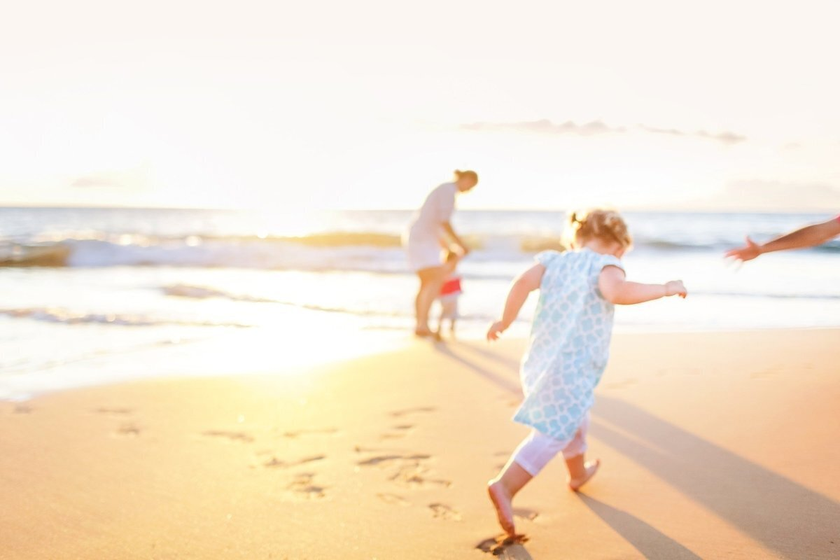 Blurry artistic image of family running on the beach in Maui