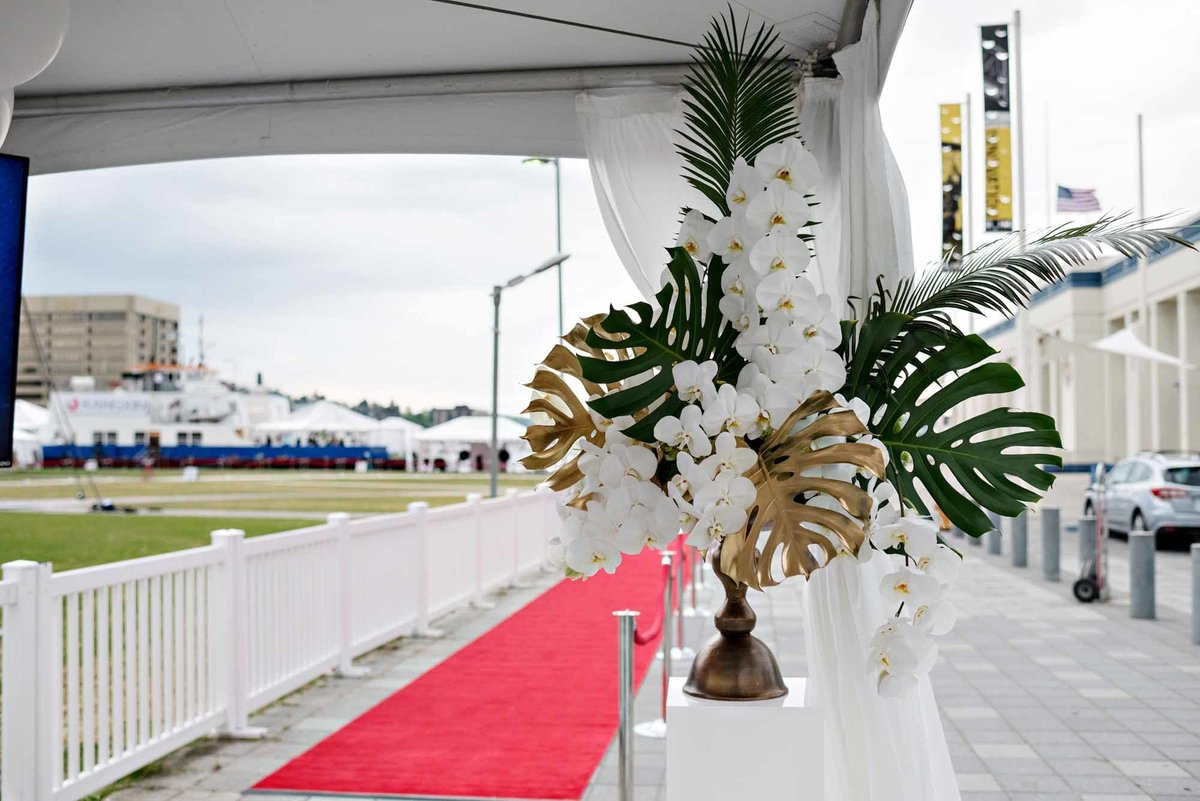 large welcome arrangement with large tropical leaves and white phaleanopsis orchids for corporate party