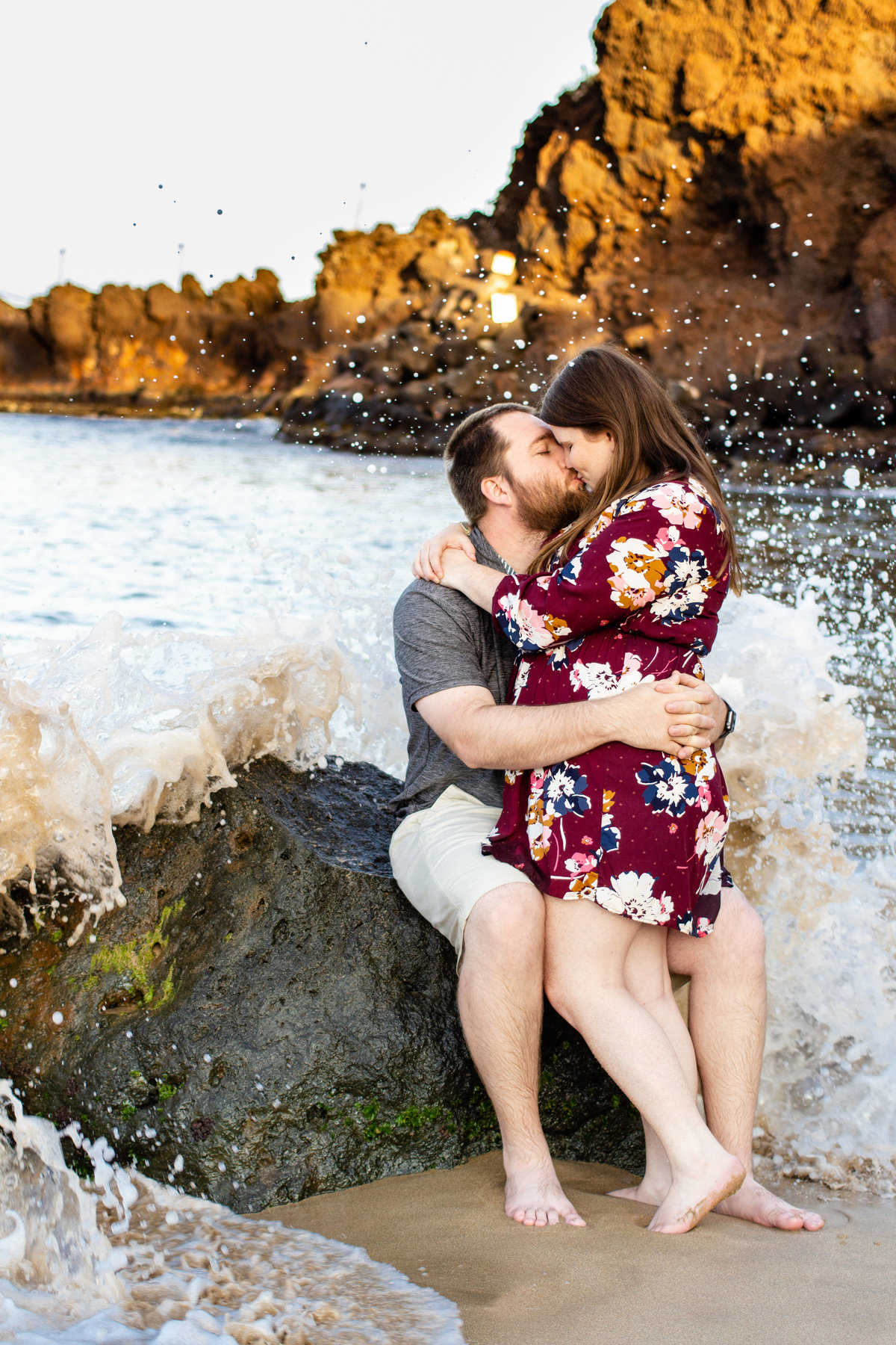 Couple braves the ocean waves in Maui, Hawaii as they go in for a kiss at their destination engagement photo session