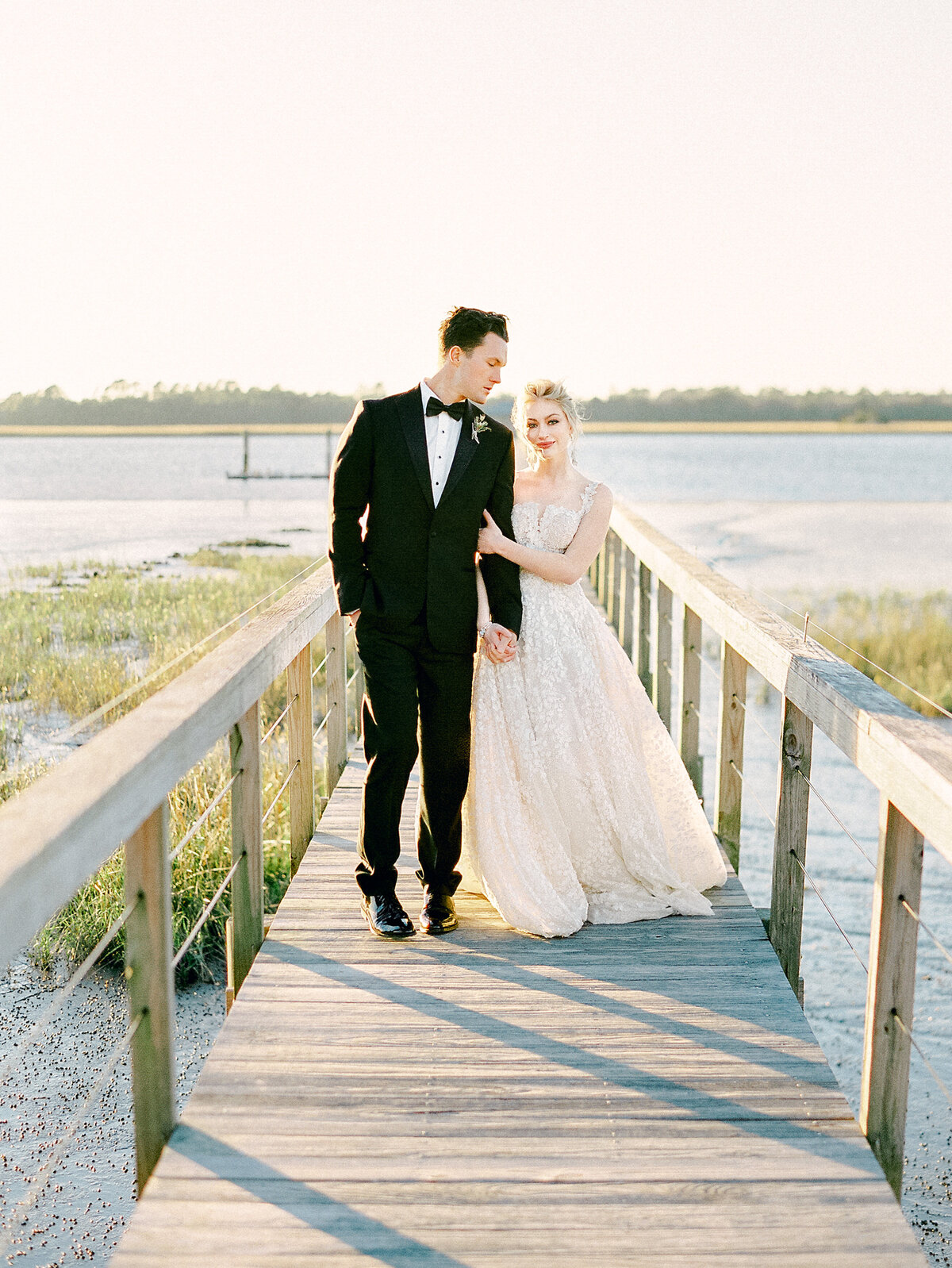 Bride and groom walking on wooden dock on river at Lowndes Grove Charleston Wedding