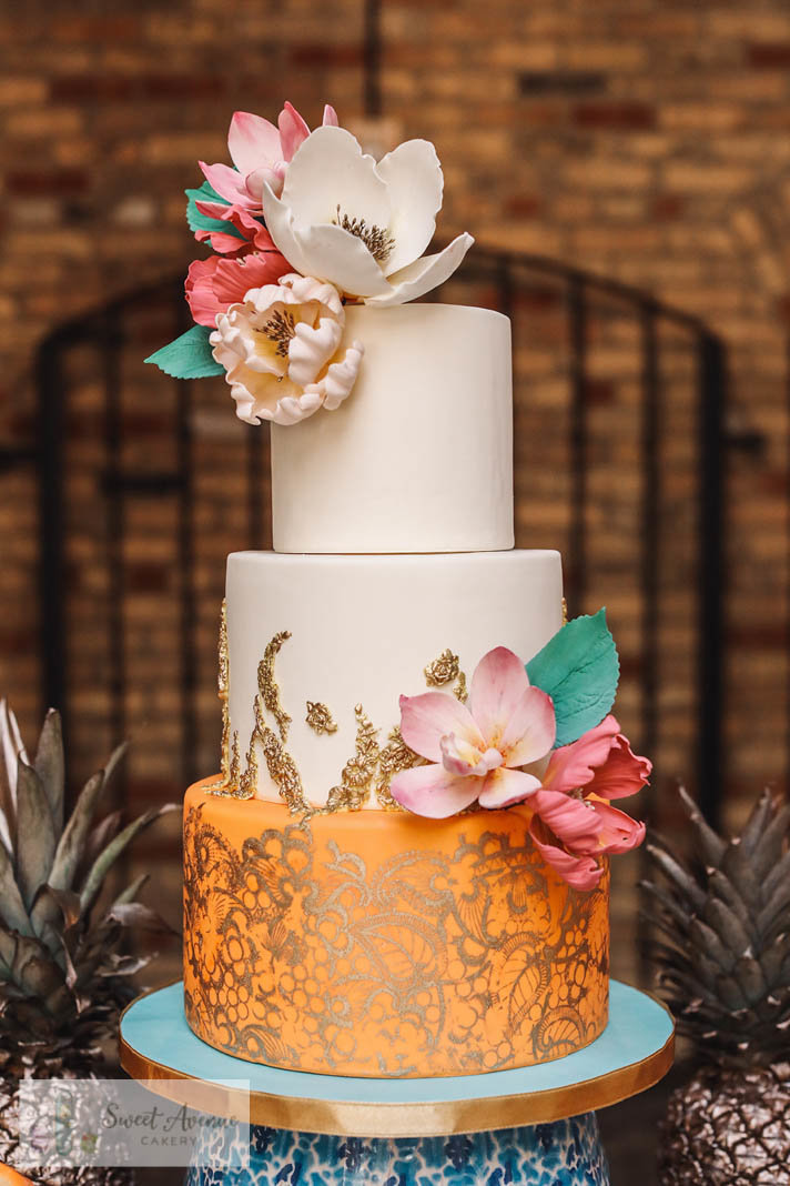 Latin inspired wedding cake with gold lace and tropical sugar flowers
