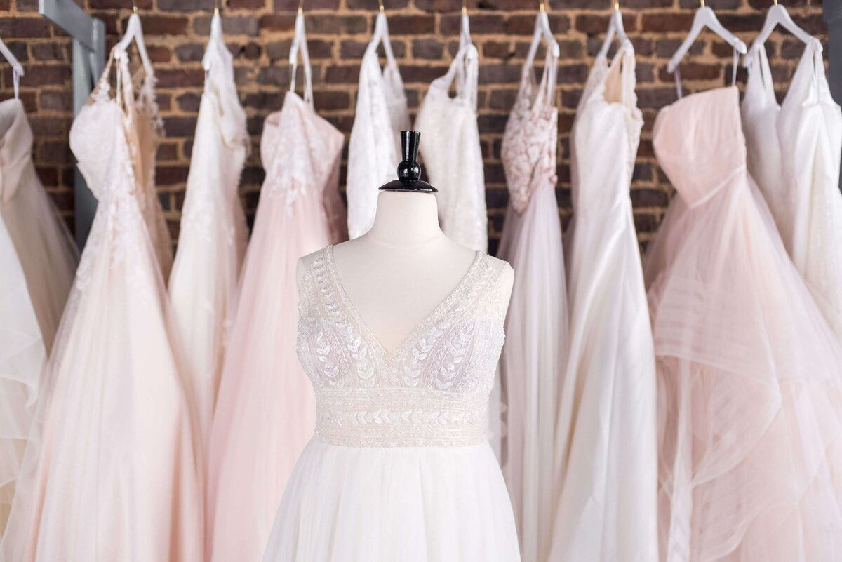 Plus size wedding dresses hanging on rack in Refined Bridal Boutique