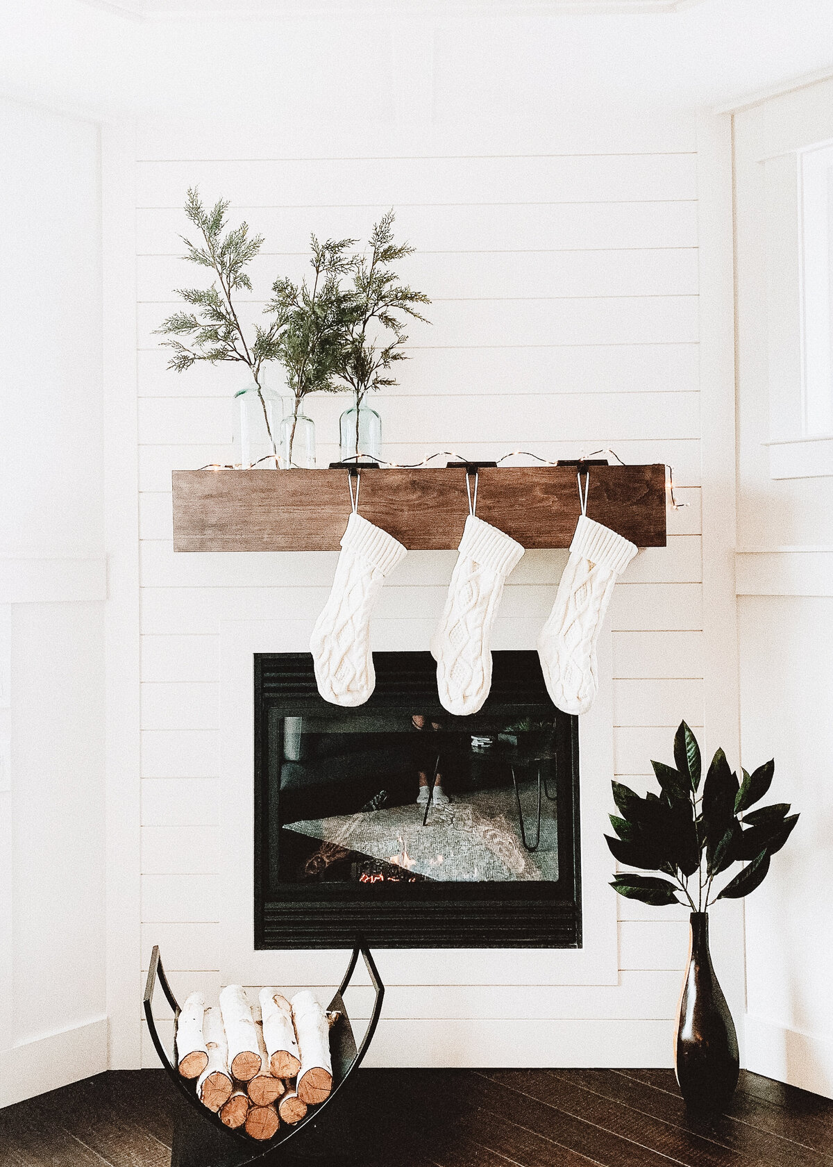 Three white stockings are hung on a chunky wooden mantlepiece in a white room.