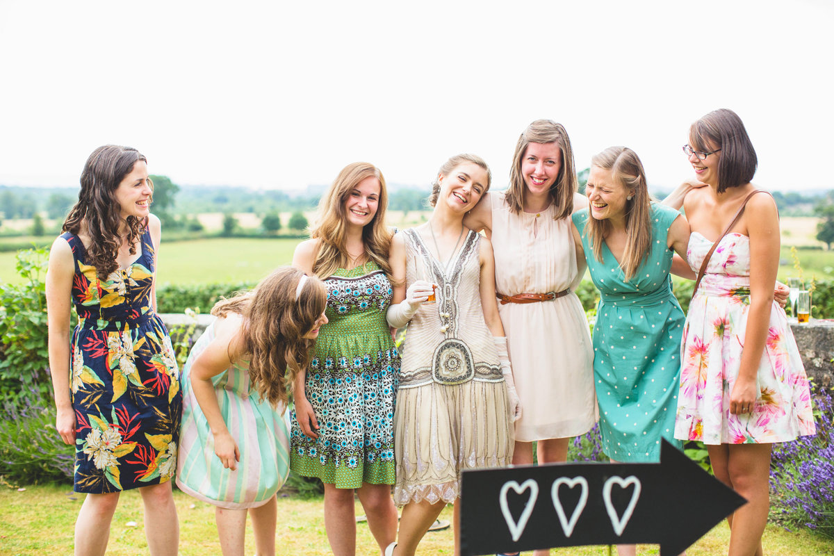 bridesmaids laughing at this barn wedding on a farm
