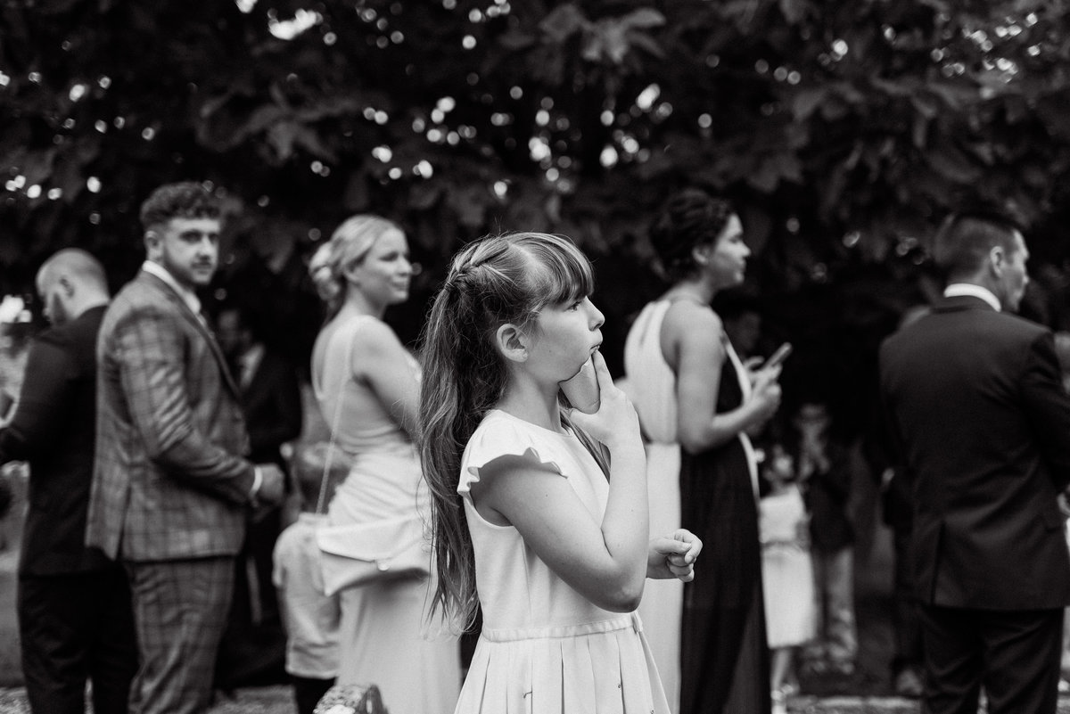 Stunning reportage style black and white wedding photo at same level side on of the flowergirl holding the confetti to her chin eagerly awaiting the bride and groom