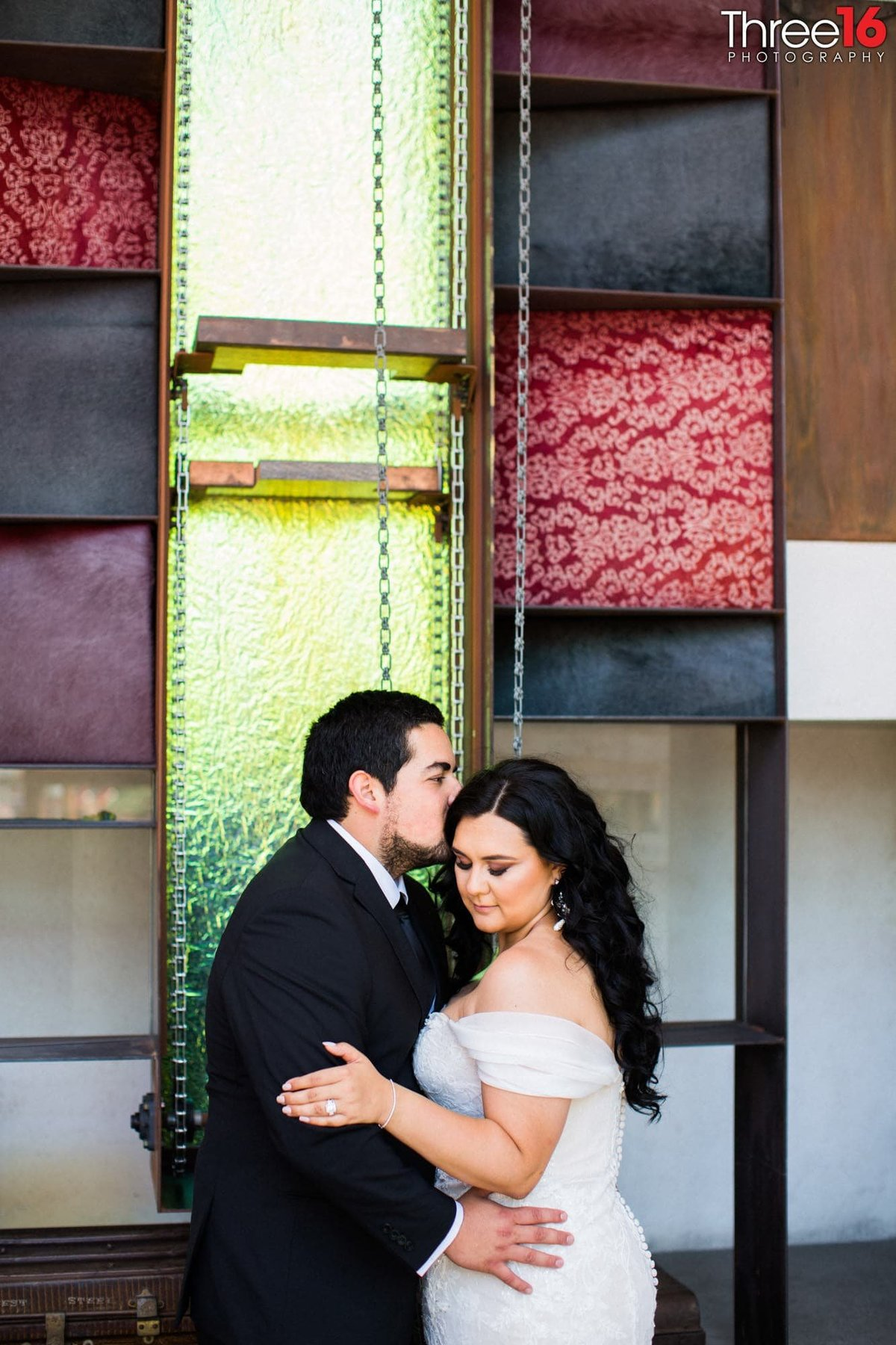 Groom kisses his Bride on the cheek during a quiet moment away from the guests