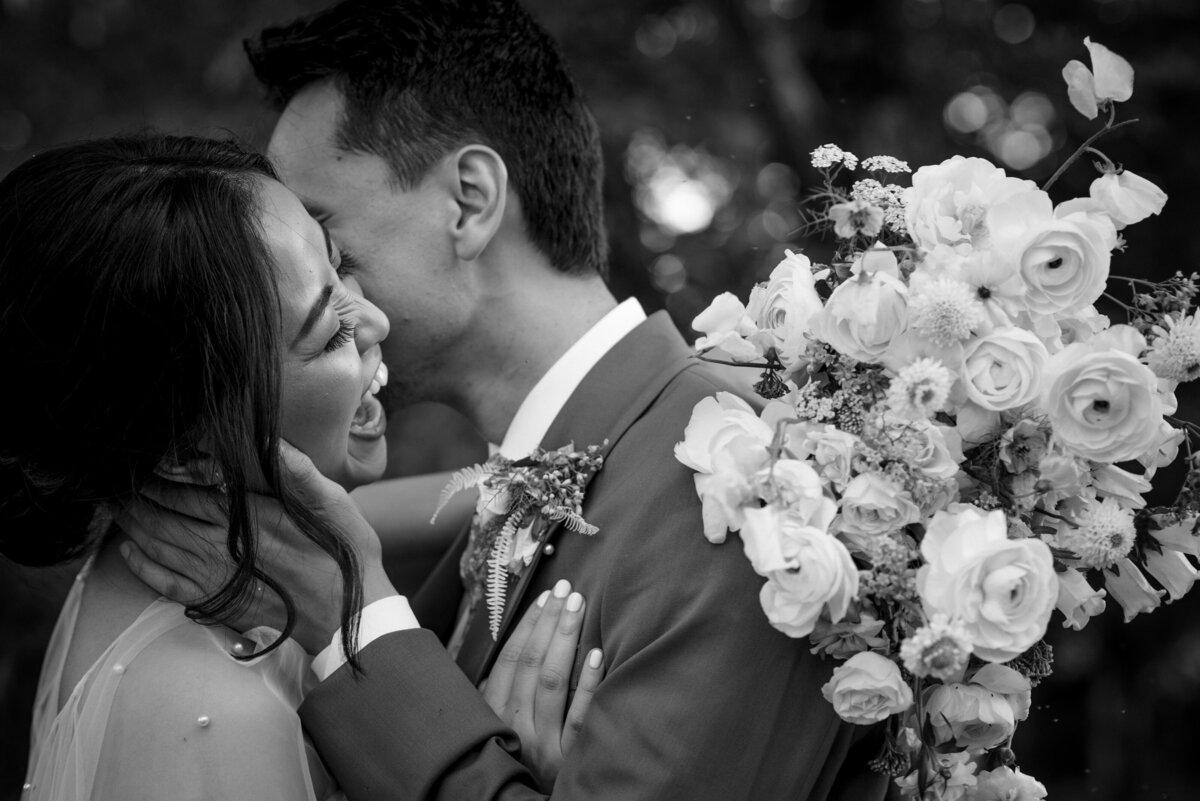 Black and white image of a laughing bride being kissed by groom