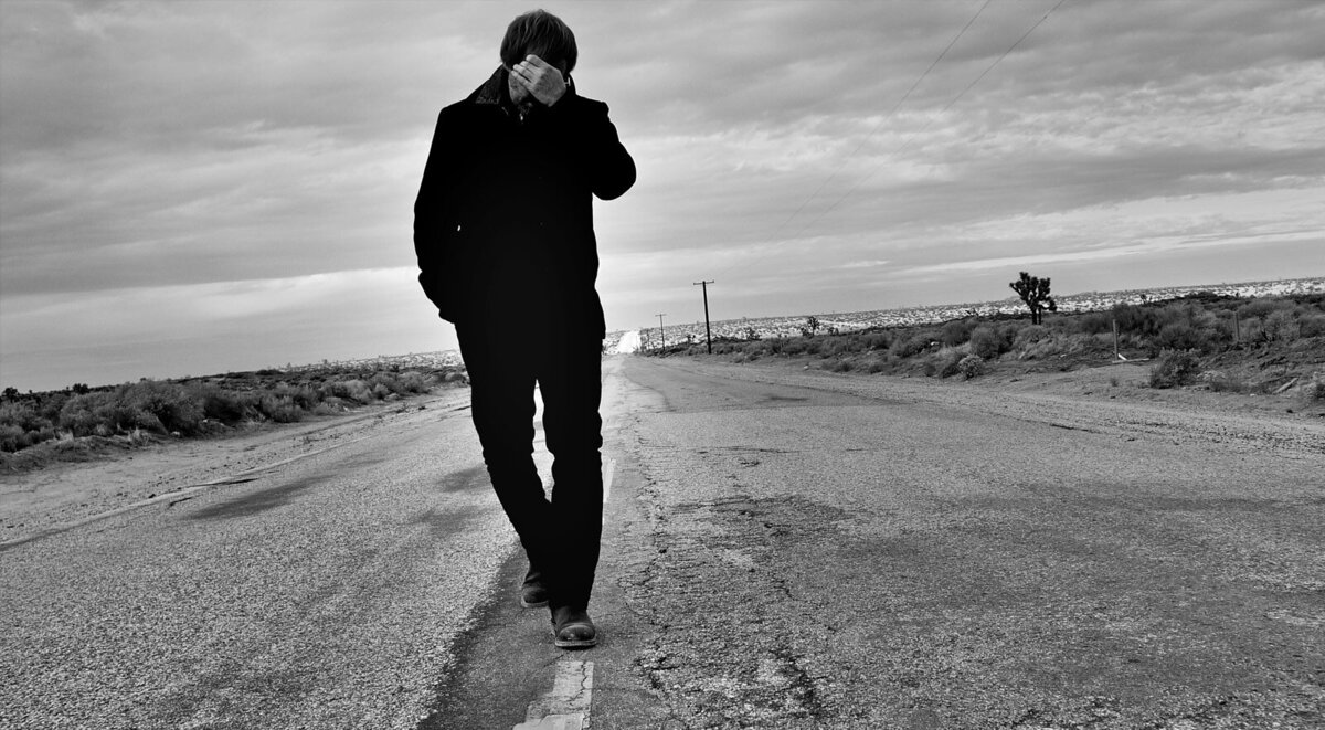 Music Portrait Musician The Mocking Bird walking down highway in desert hand covering his face while he looks down black and white image