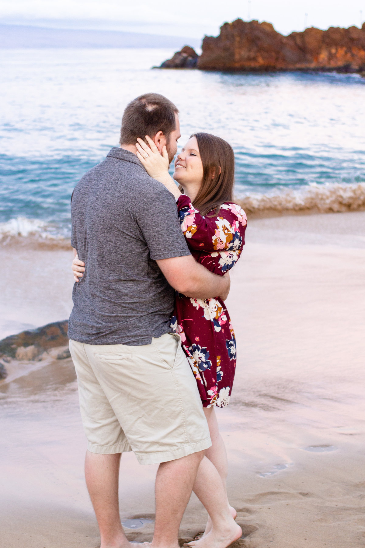Couple looks at one another on beach in Maui, Hawaii during their destination engagement session