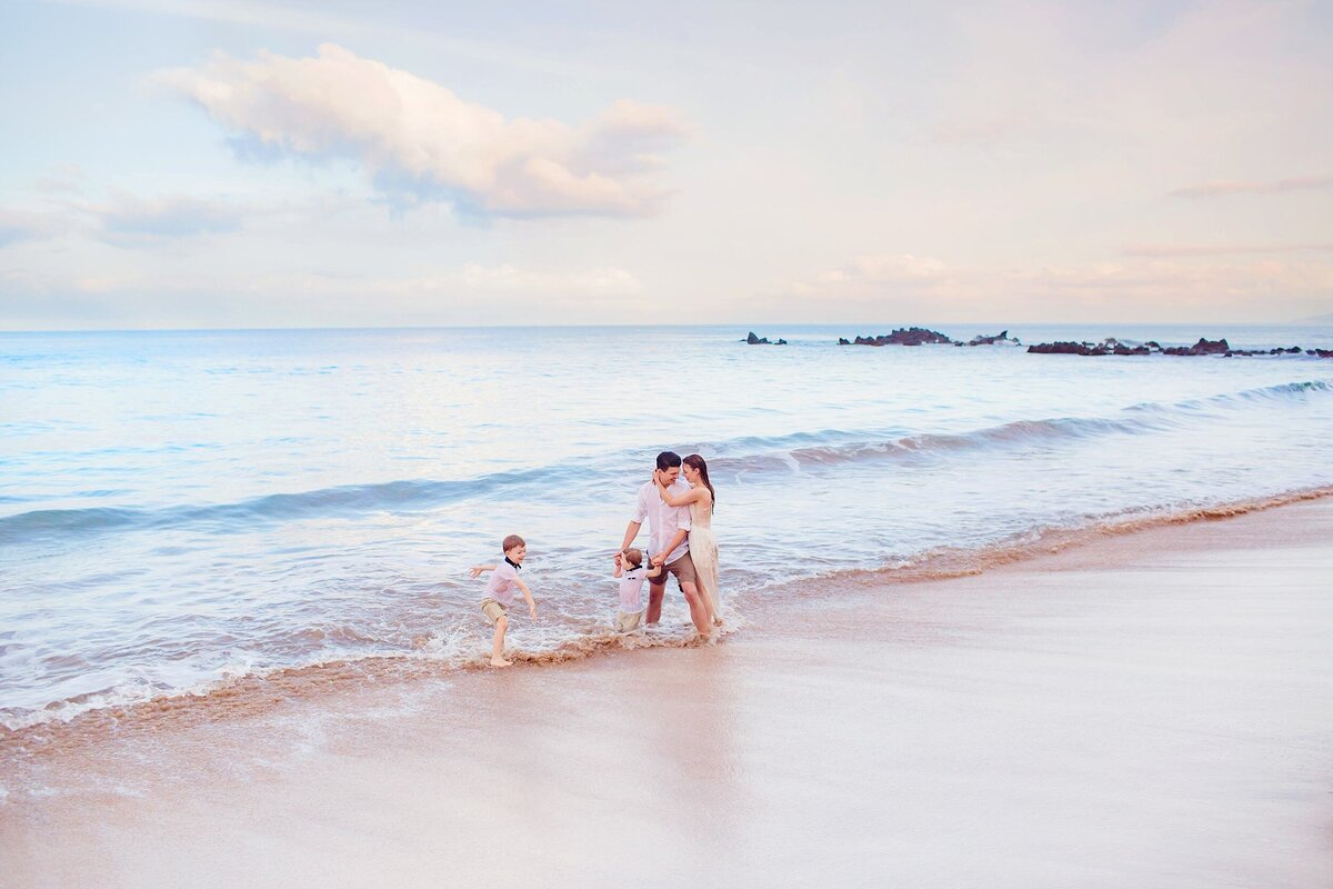 Two boys play as mom and dad pose on the beach in Maui during their family photography session