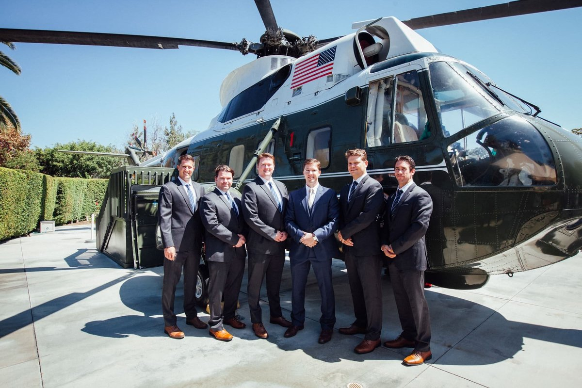 Groomsmen pose in front of the helicopter on the grounds of the Richard Nixon Library