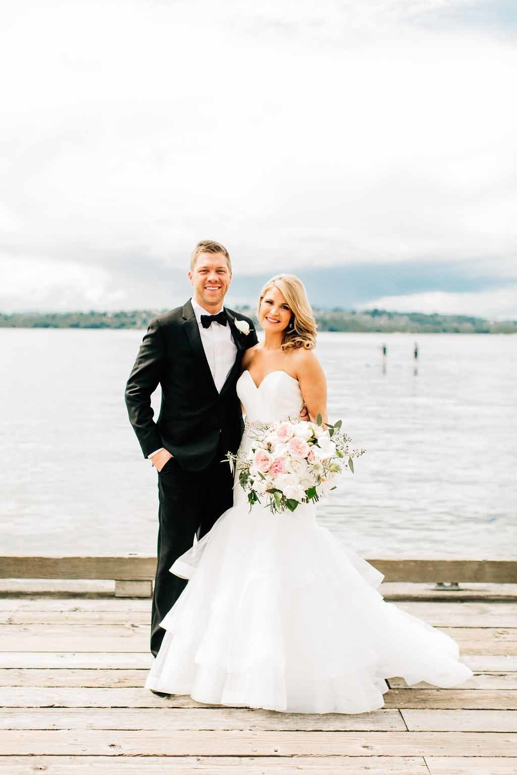 Beautiful bride and groom standing in front of Lake Washington before their outdoor tent wedding.