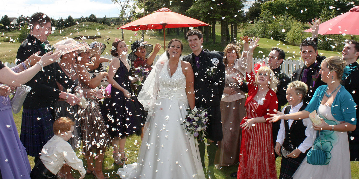 group photograph as confetti is thrown over a bride and groom