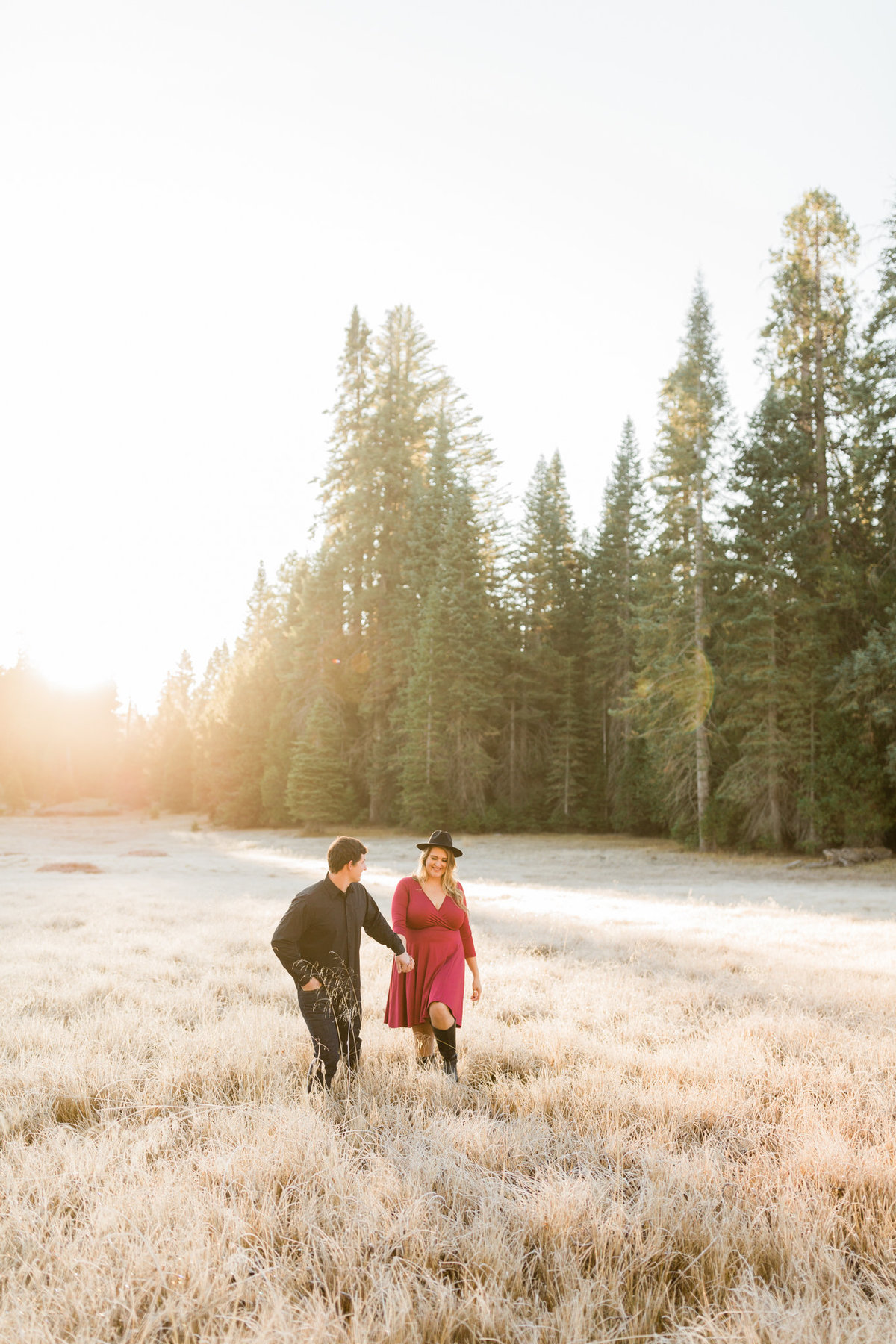 couple holding hands and walking through a grassy meadow