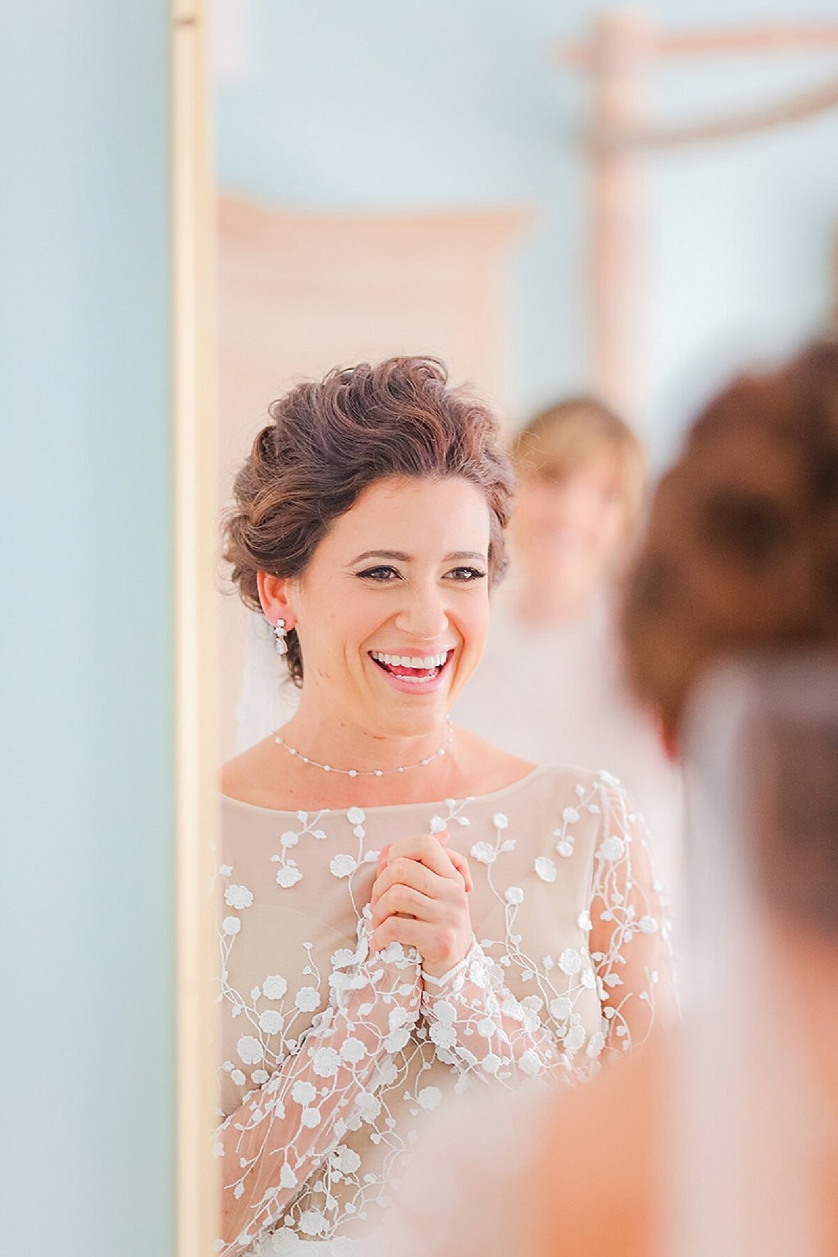 Bride at White Orchid Wedding House stares into the mirror enthusiastically