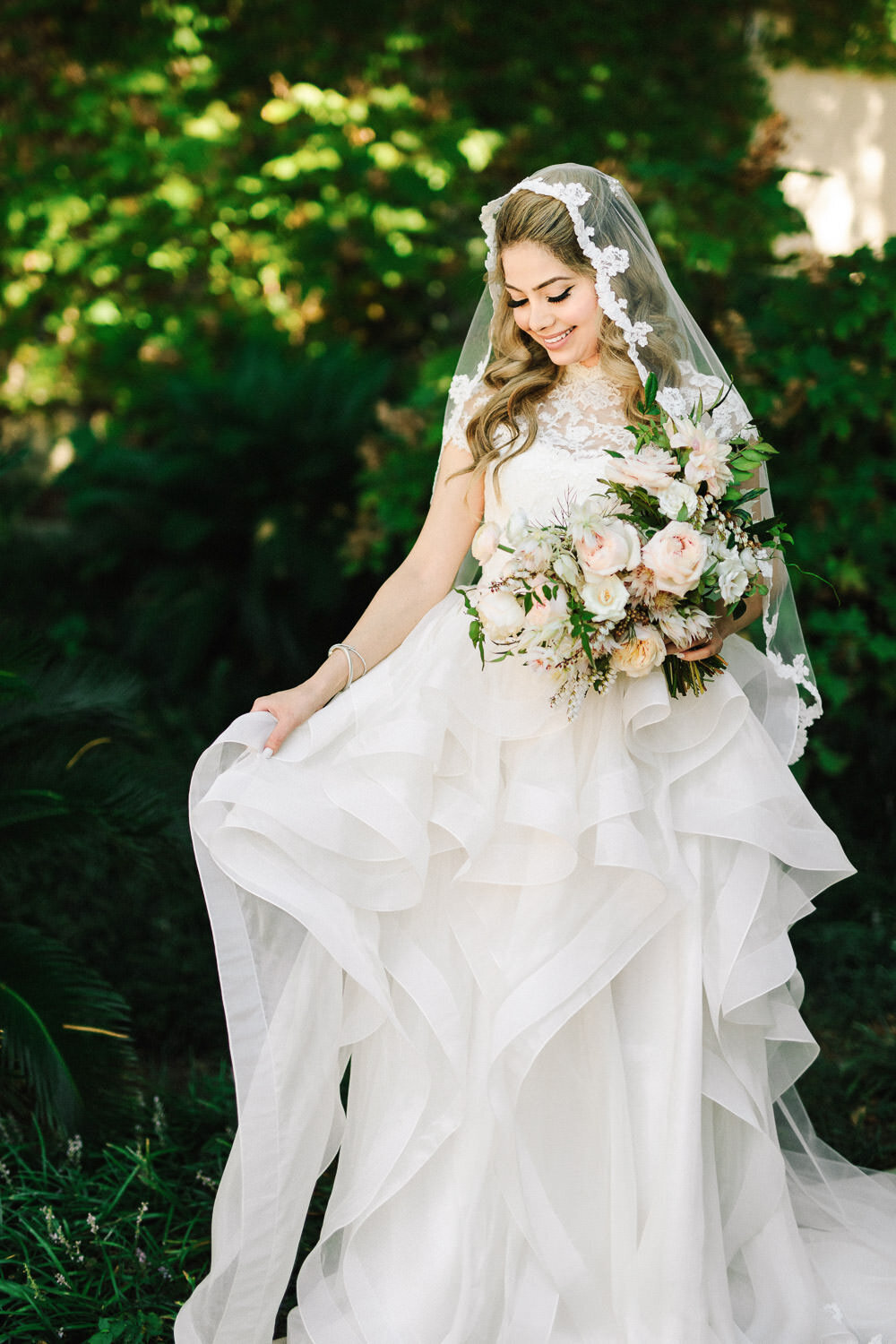 Bride in white wedding dress and veil holding bouquet in front of greenery