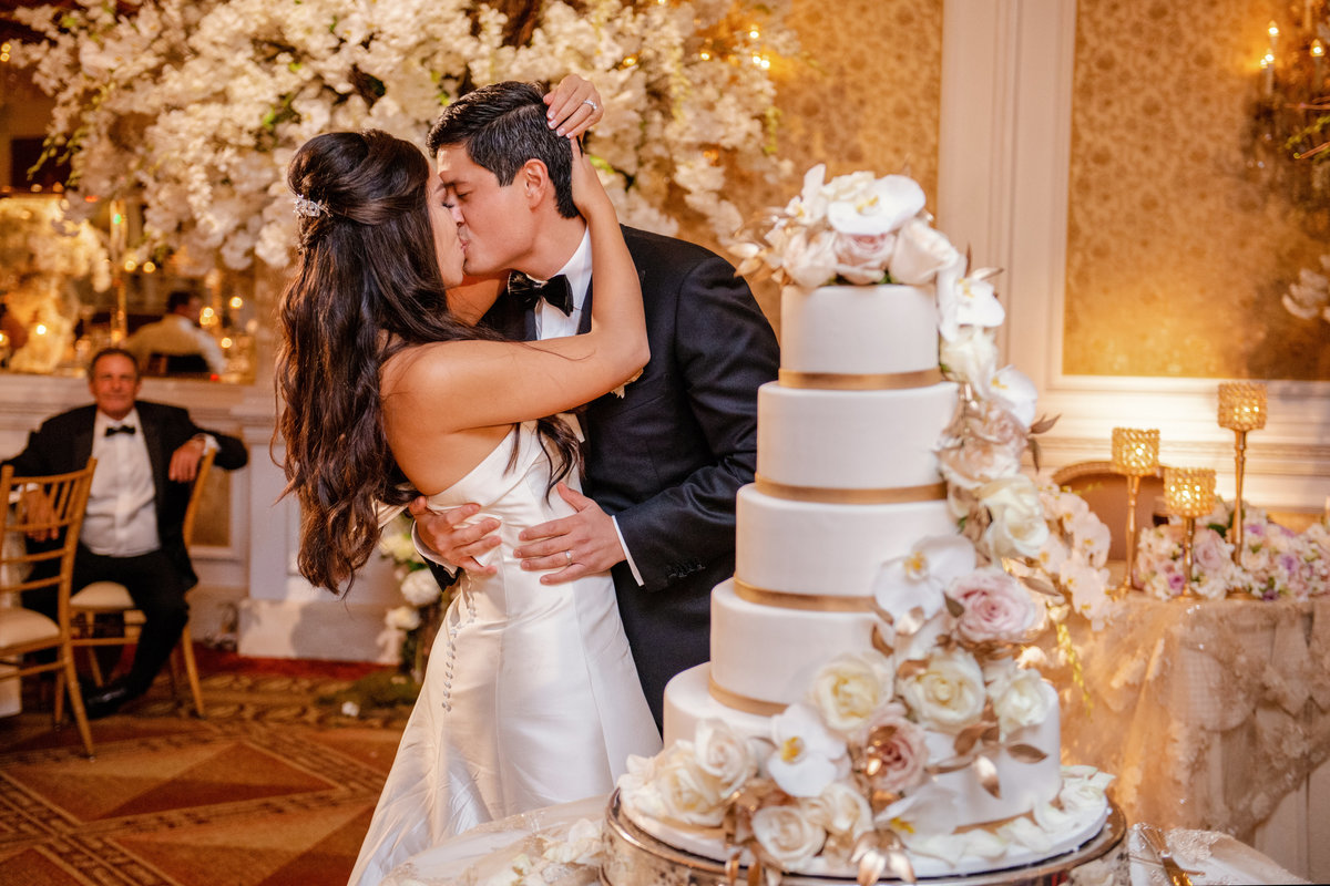 photo of bride and groom kissing behind wedding cake during wedding reception at The Garden City Hotel