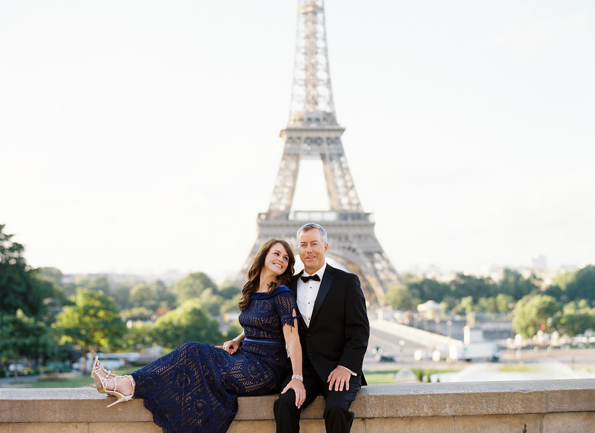 Married couple in evening wear celebrate their anniversary with photos in front of Eiffel Tower