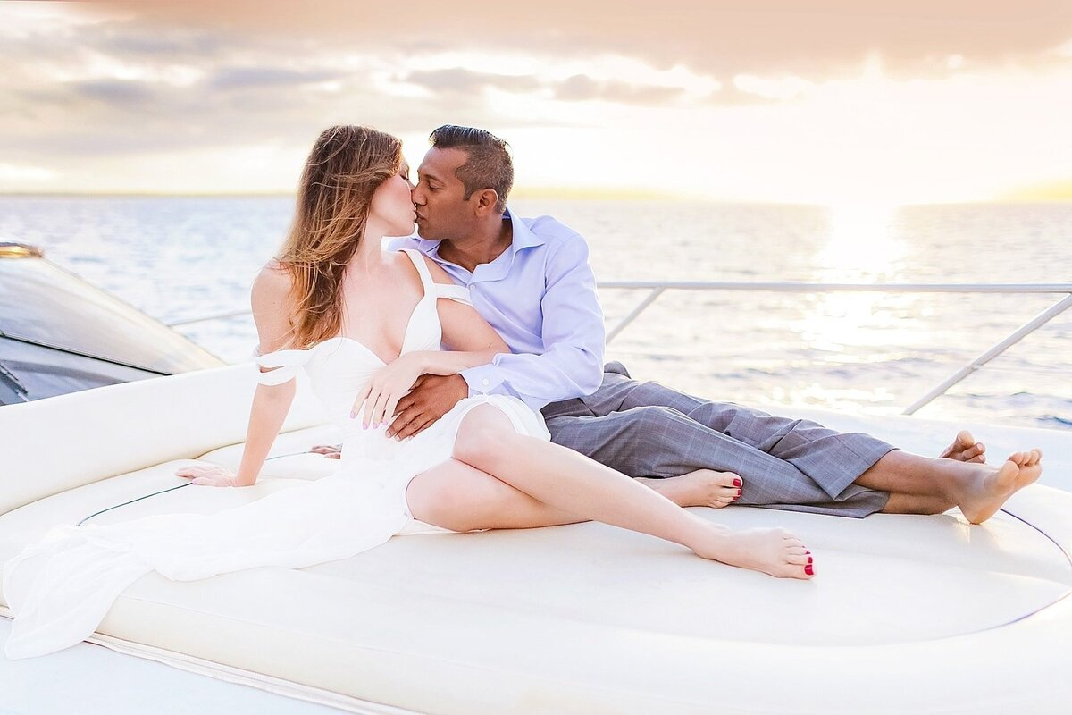 Bride and groom kiss aboard a private yacht after their Maui wedding day