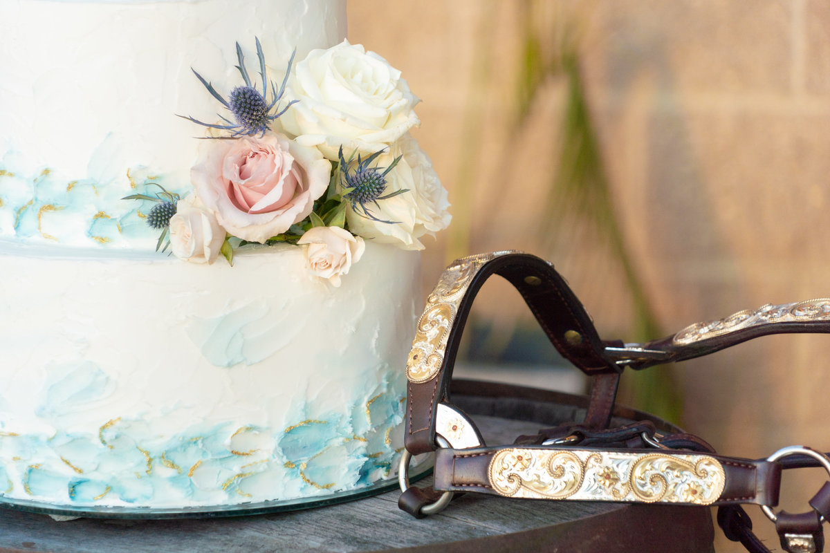 White wedding cake with light pink and white roses and teal markings next to a leather and gold bridle