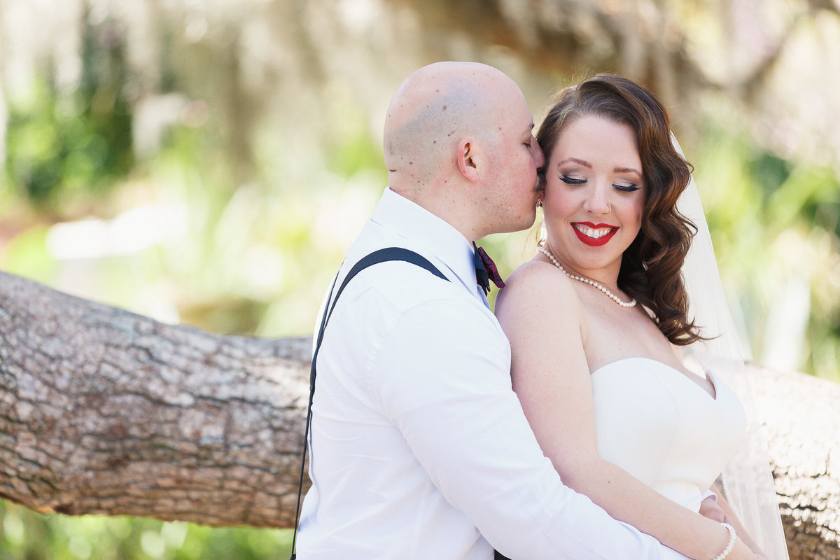 Groom Kisses Bride on the Cheek at their Riverside Wedding Photo Shoot in Jacksonville Florida
