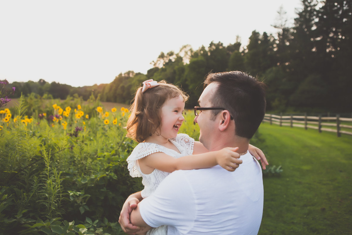 Father hugging and laughing with daughter in field {Milton Family Photographer}
