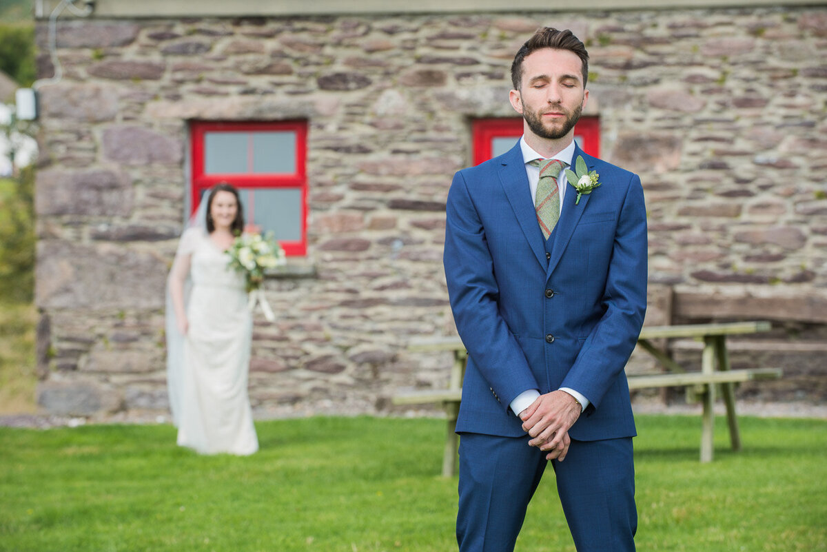 Groom wearing a blue wedding suit and green, tweed tie waiting for a first look of his bride who is wearing a vintage, beaded wedding dress holding a white and green bouquet outside an old stone cottage at Westcove House, Kerry