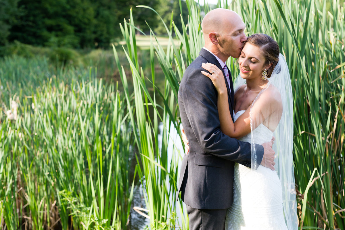The couple stand by the pond and tall grass at the Pierce House in Lincoln MA