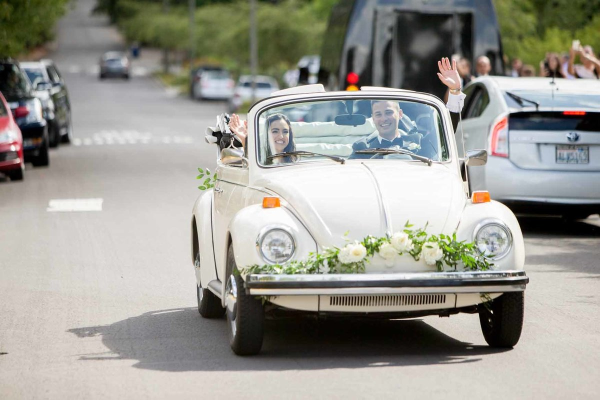 Newly weds in vintage get-away car decorated with white flowers