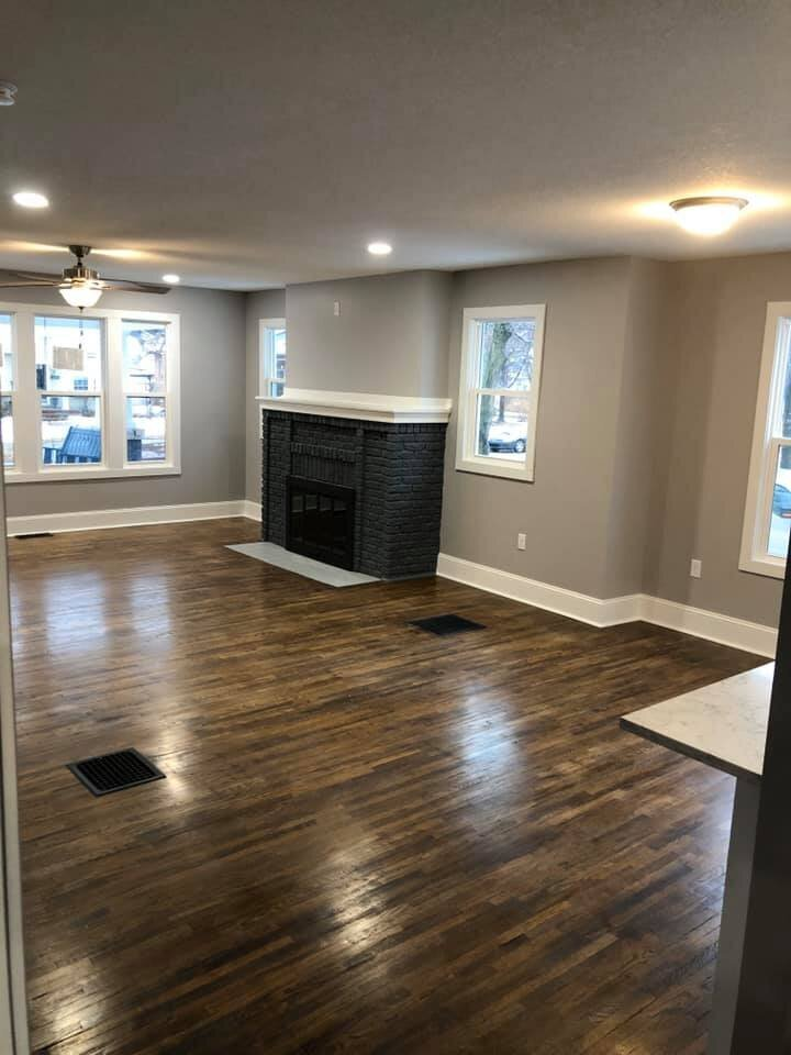 Remodeled living room with grey walls and dark hardwood floors