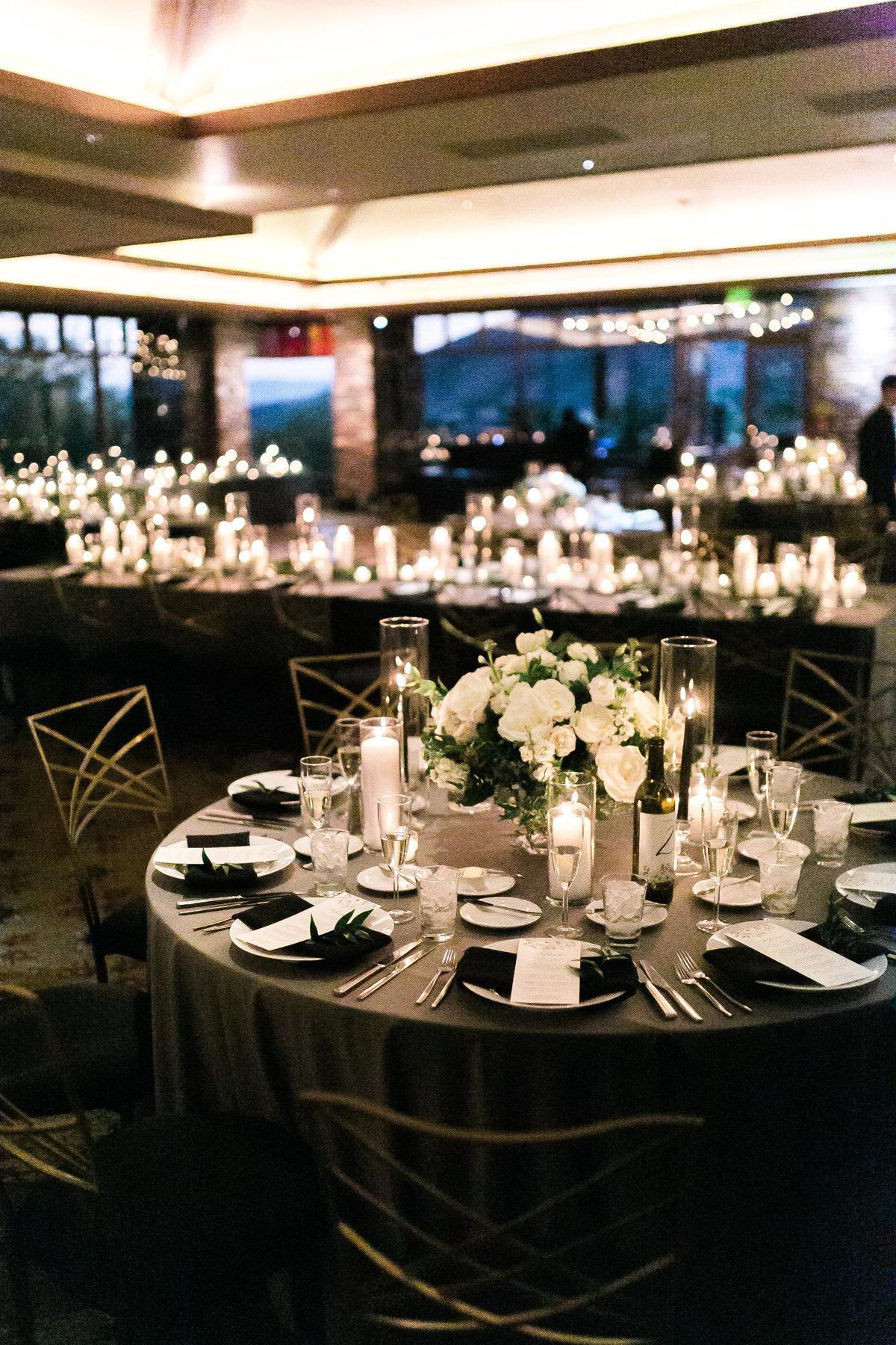 wedding reception with a ton of candles and grey velvet linen