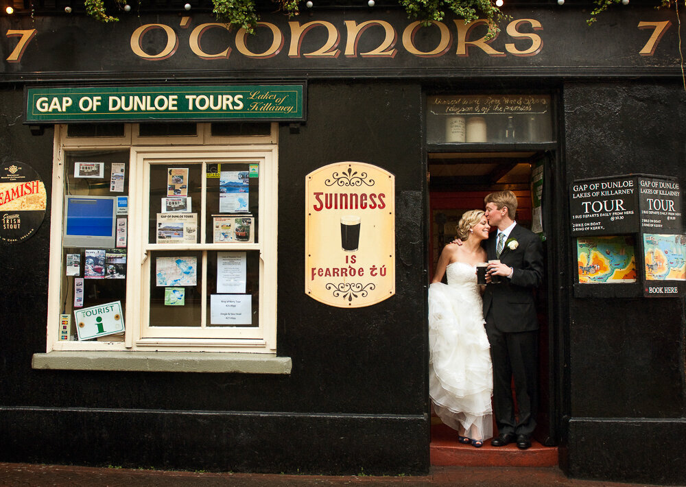 bride wearing a tulle ballroom dress kissing her groom with a black suit in the doorway of O'Connors pub, Killarney