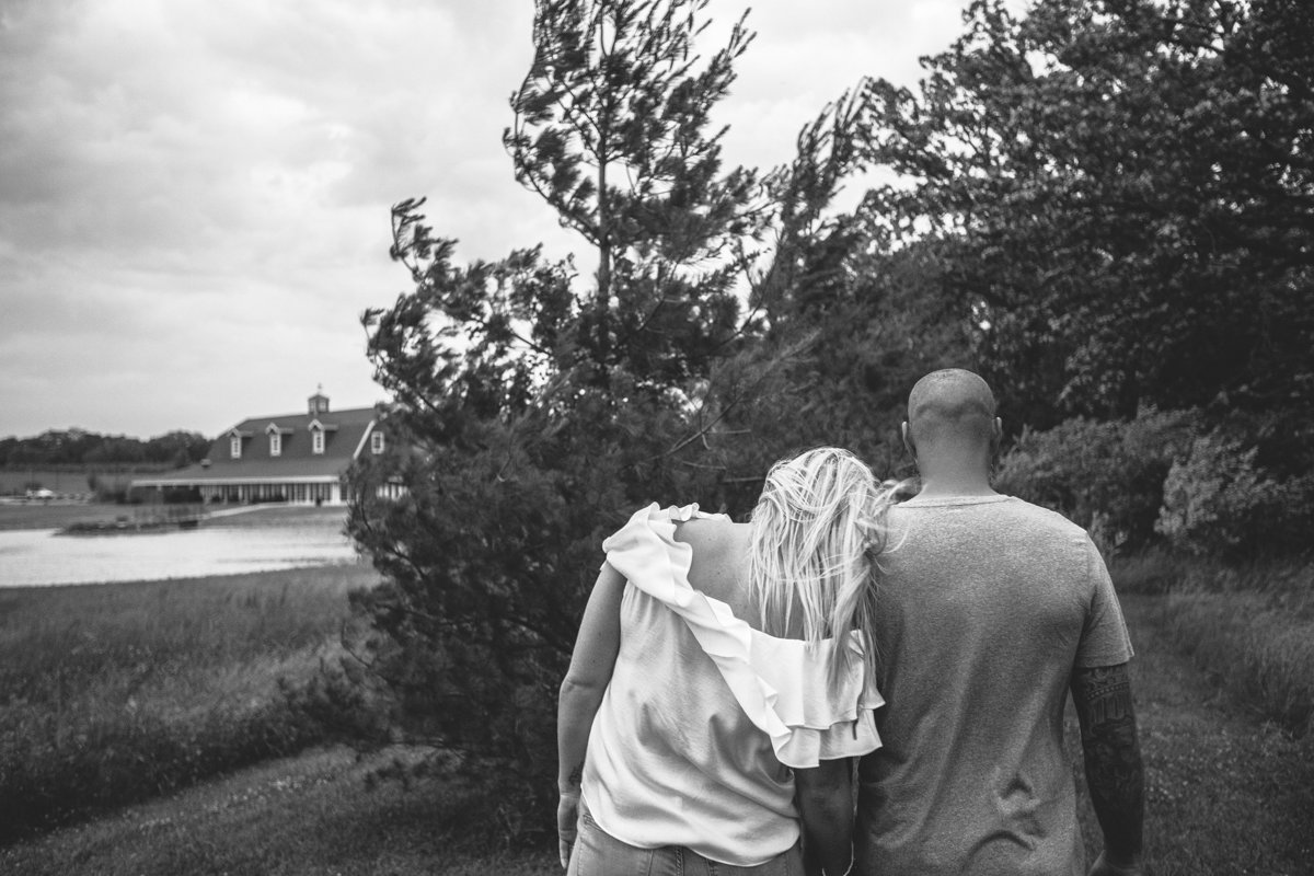 couple walking by a barn during their engagement