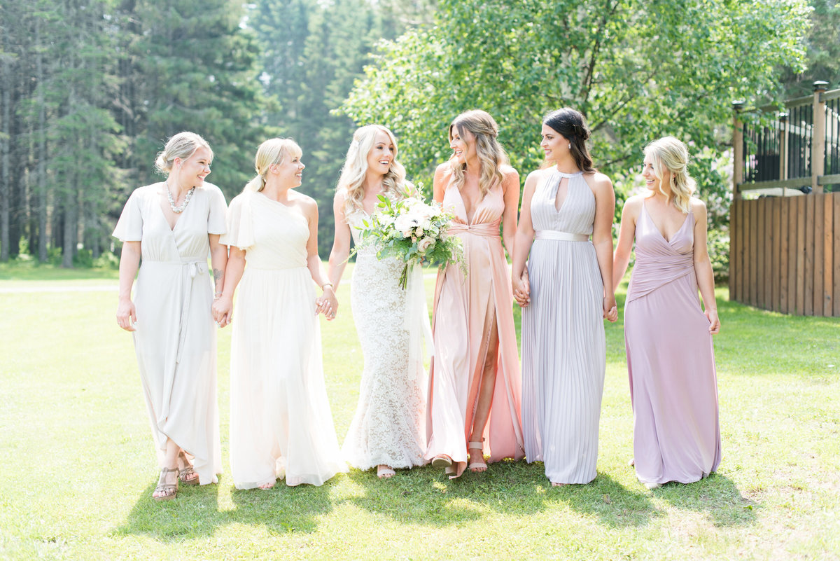 Bride and her bridesmaids walk hand in hand before wedding at Stepstone Centre in Thunder Bay