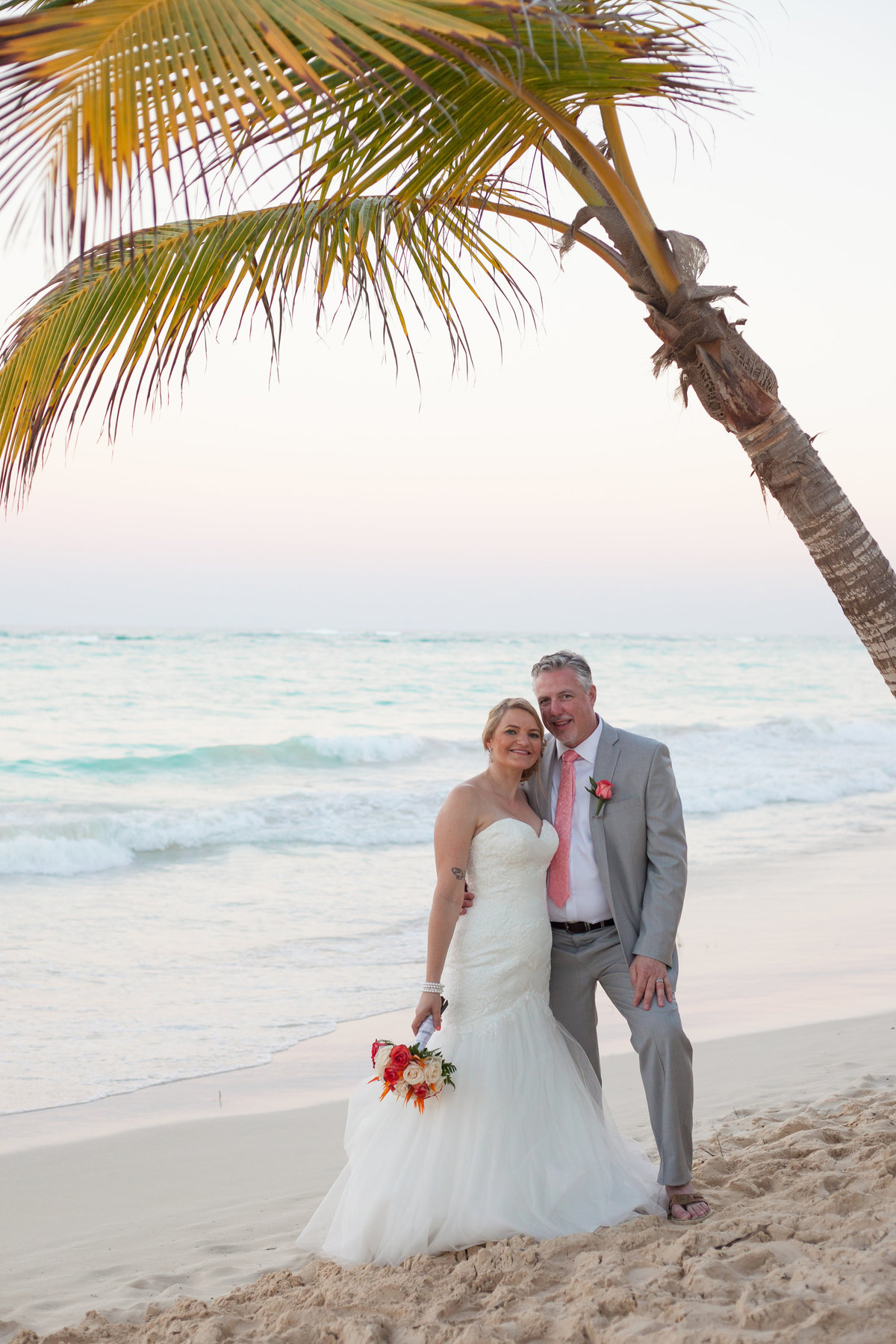 couple walks on punta cana beach after reciting vows for destination wedding
