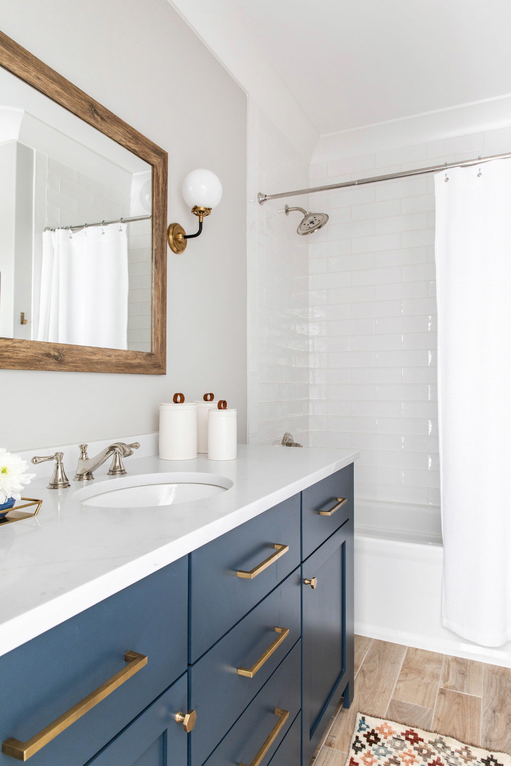 Benjamin-Moore-Blue-Note-Vanity-with-Brass-Hardware-and-Circa-Lighting-Sconce-2