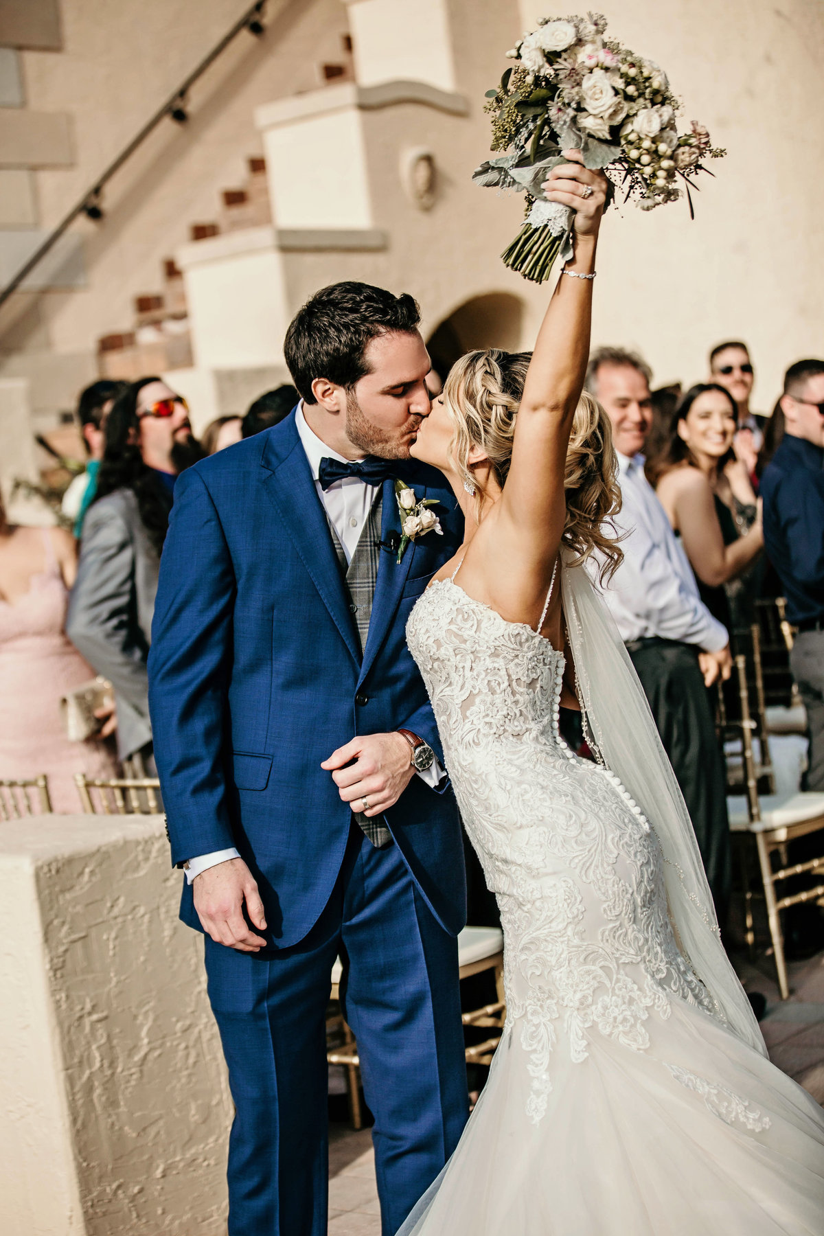 An image of a bridal couple happily kissing after their marriage ceremony as the bride, in her beautiful dress, holds up her bouquet while the guests smile and look on by Garry & Stacy Photography Co - Tampa wedding photographer