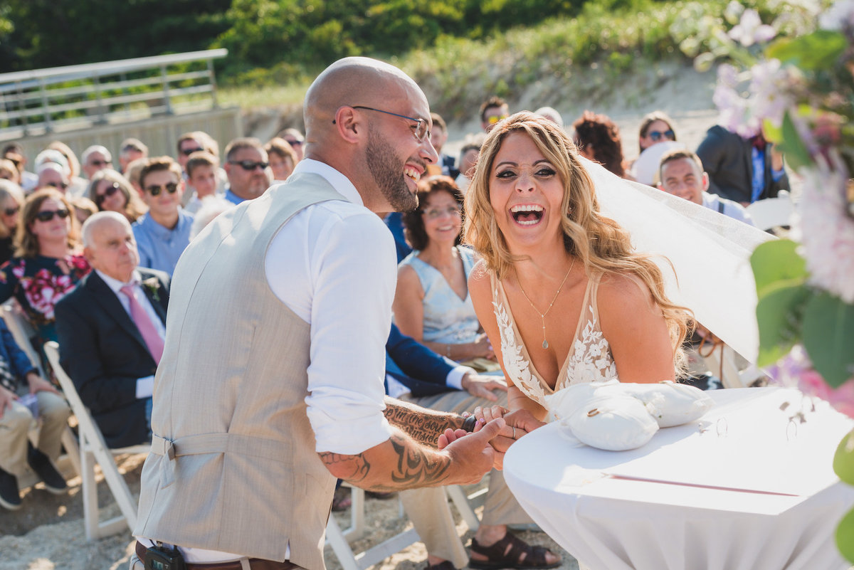bride and groom laughing during wedding ceremony on the beach at Pavilion at Sunken Meadow
