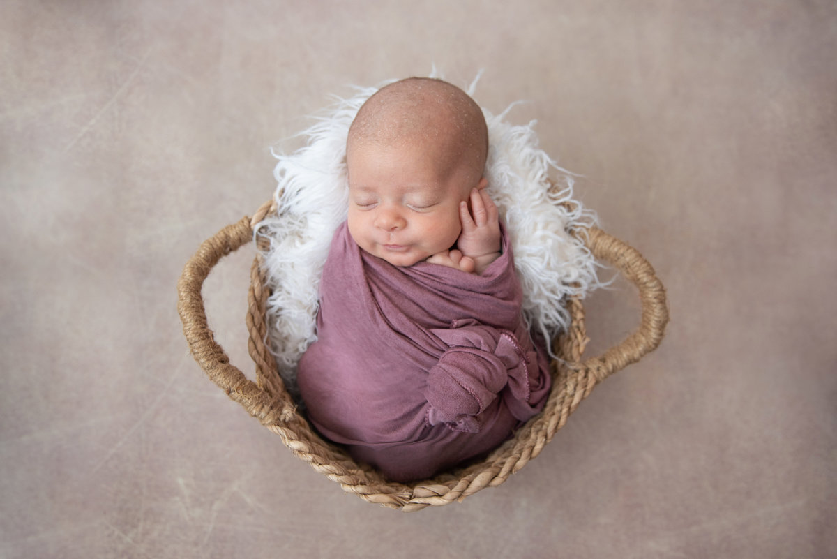 4 week old newborn swaddled and posed in basket prop