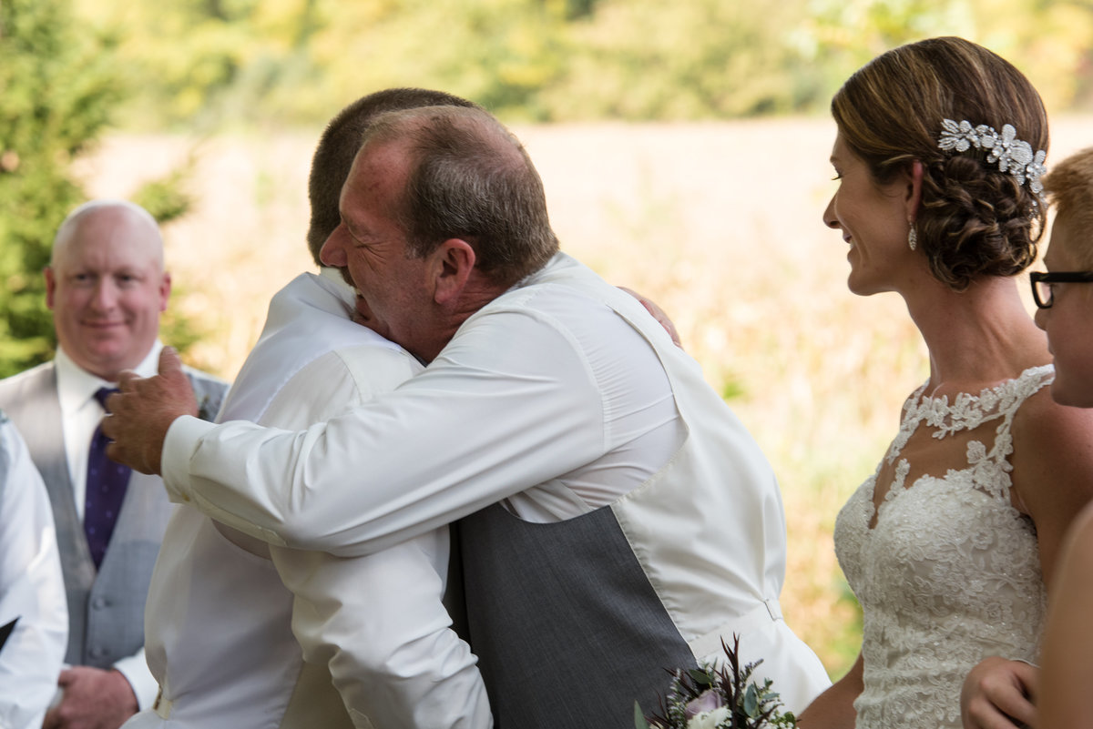 father hugs groom