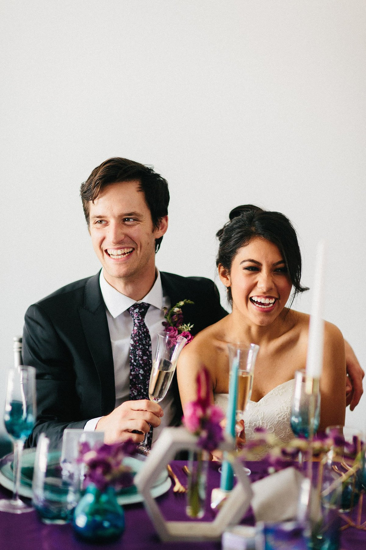 Smiling bride and groom at purple and teal wedding reception at Factory Atlanta