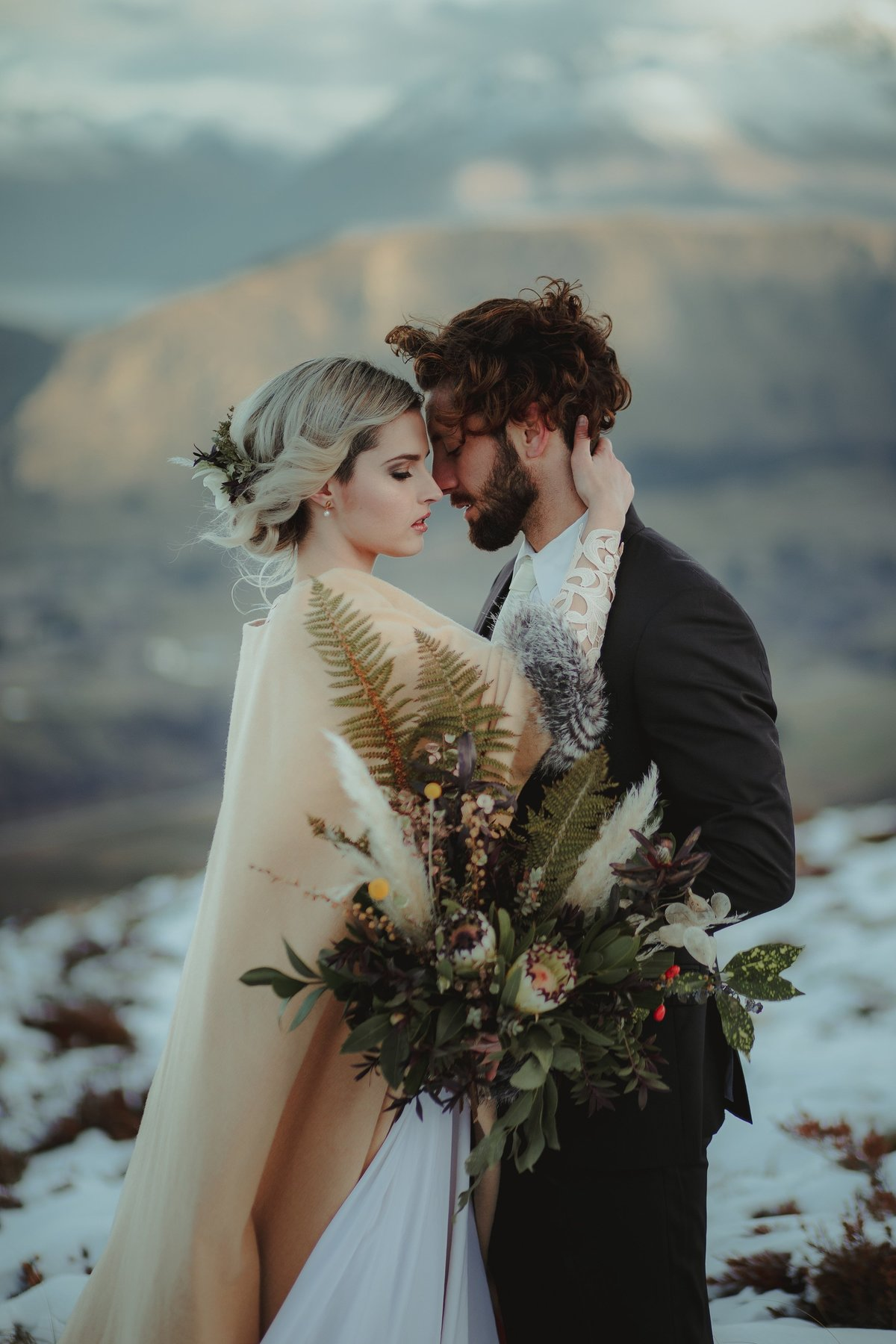 Bride and Groom holding each other close surrounded by snow