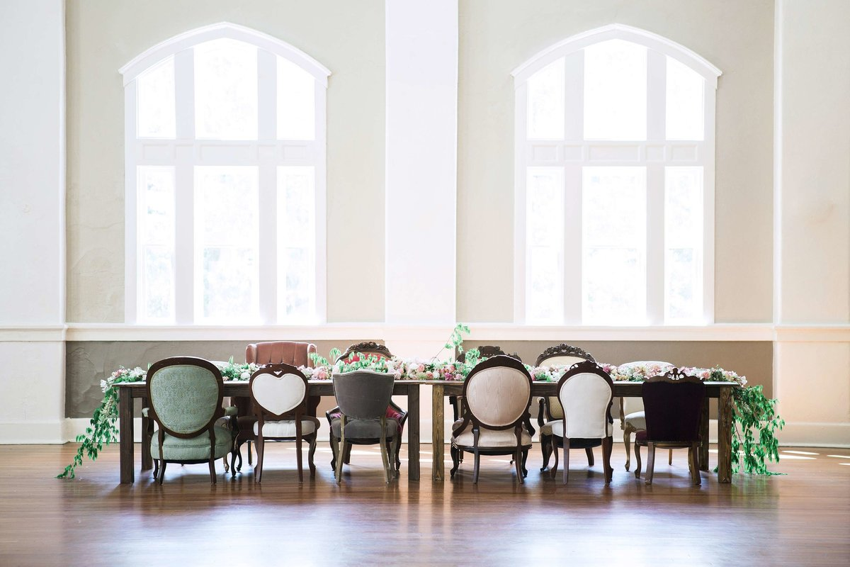 A long table with various vintage chairs.