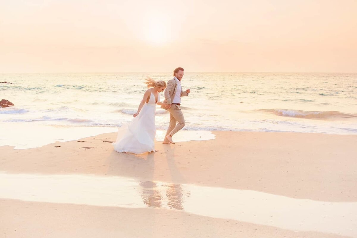 Bride and groom running hand-in-hand after their Maui elopement