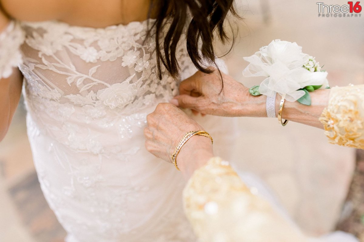 Bride getting buttoned up in her wedding gown