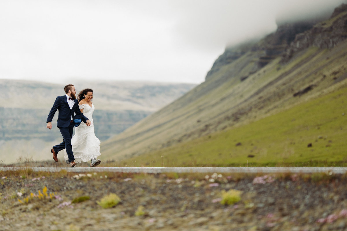 Bride & groom run down the road after their Iceland wedding