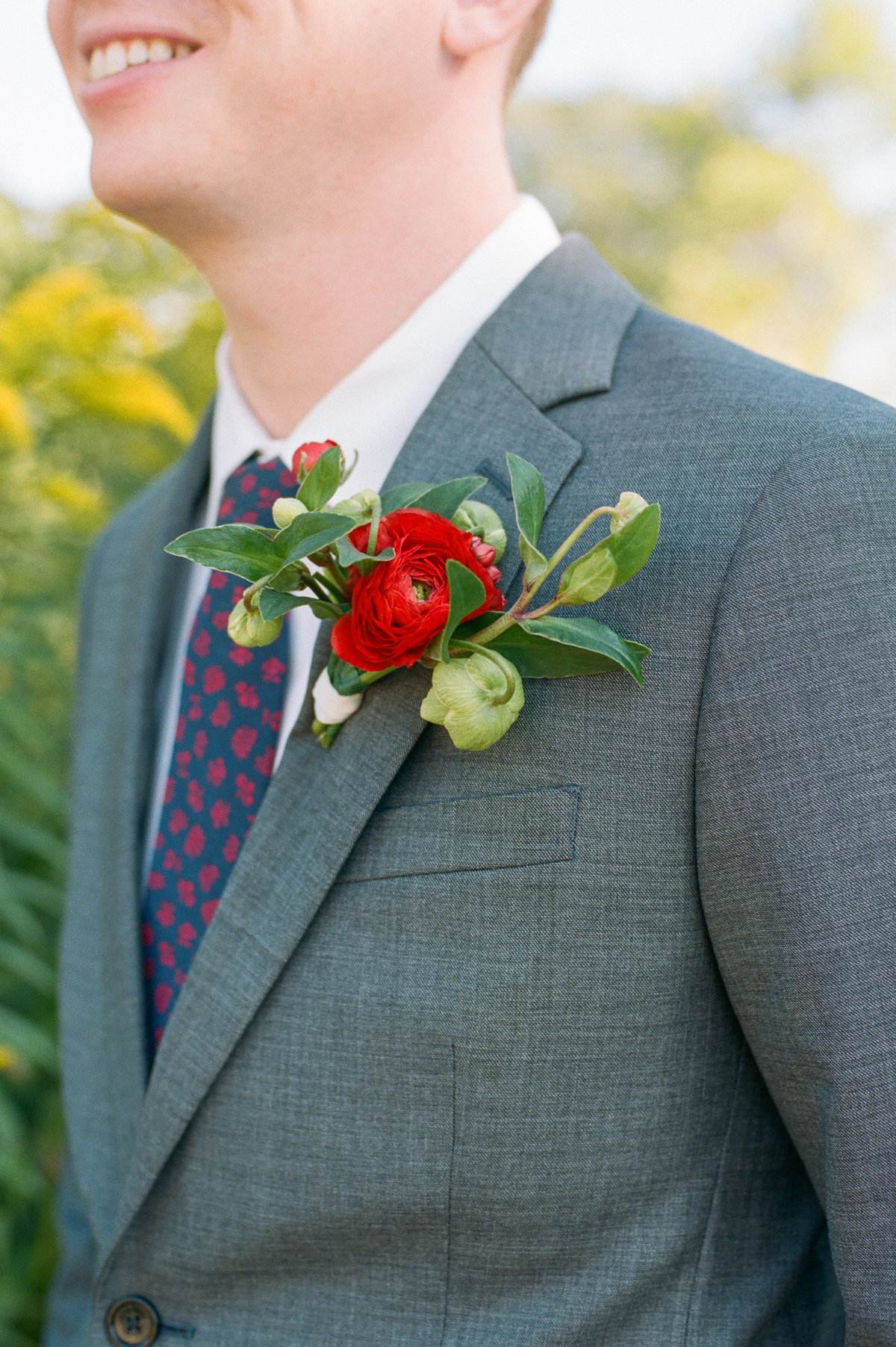 groom in grey suit with red and green boutonniere