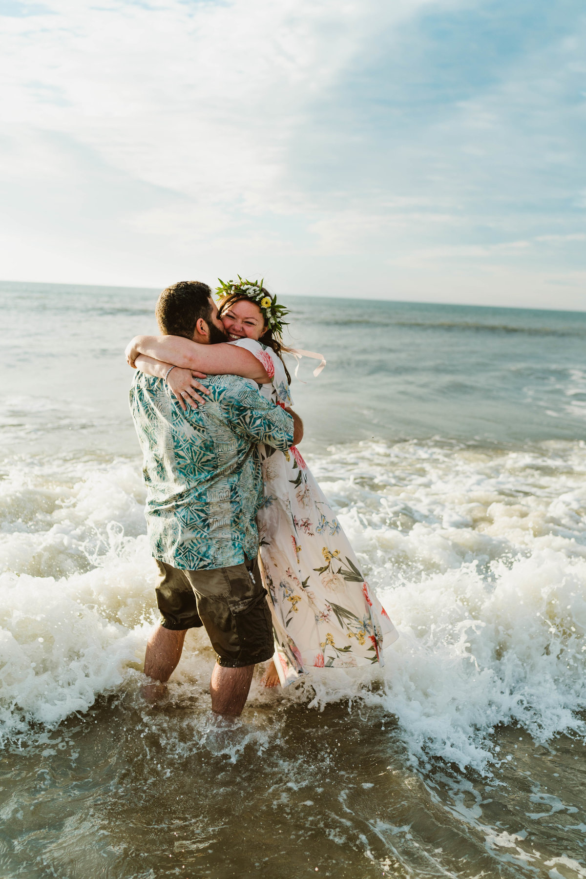 bride and groom embracing in the ocean after eloping