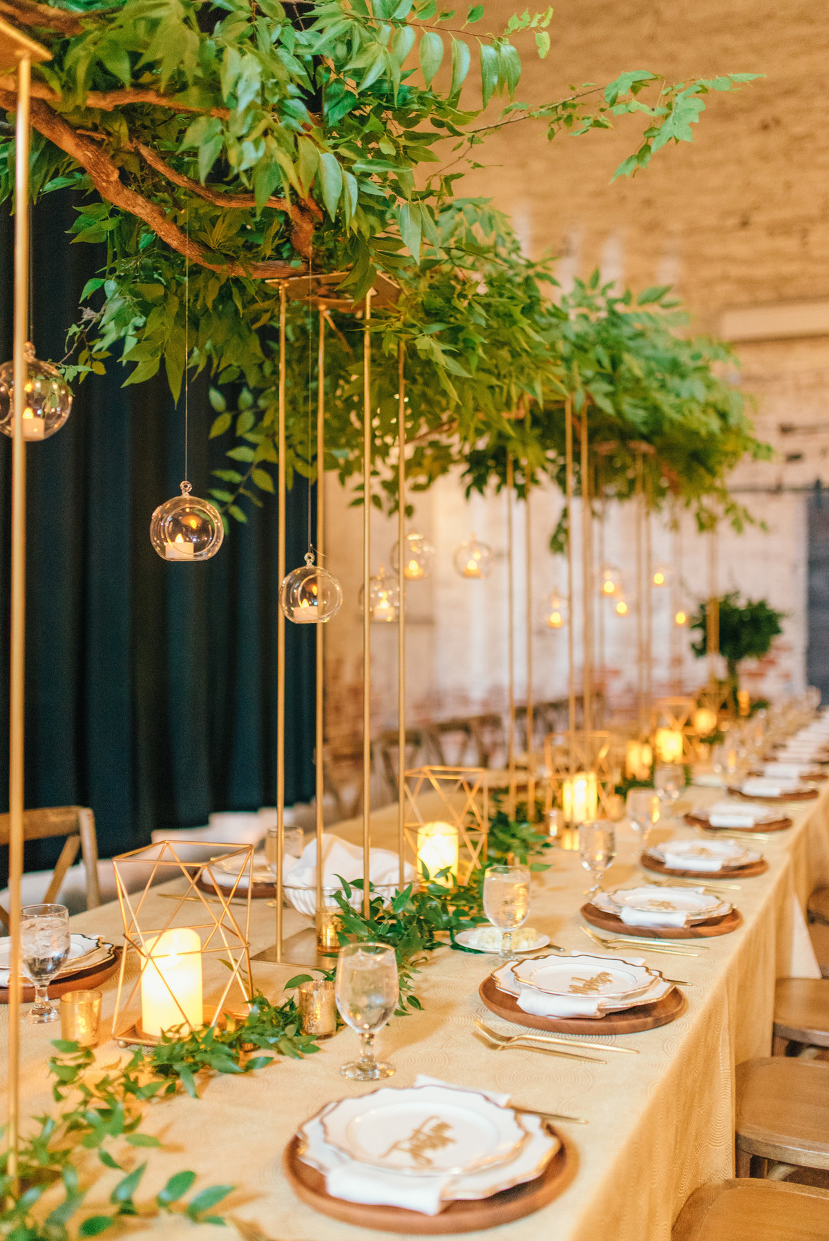long headtable with tall greenery centerpieces on gold stands with hanging orbs for lighting